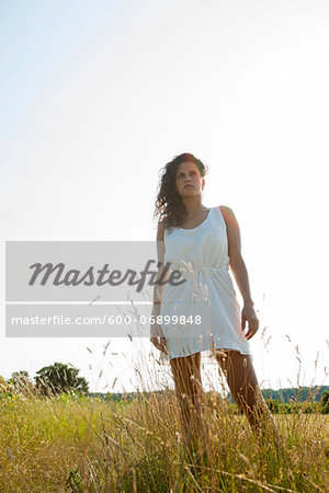 Teenaged girl standing in field on summer day, looking into the distance, Germany Stock Photo - Premium Royalty-Free, Image code: 600-06899848