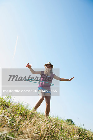Girl using hula-hoop outdoors on hill, Germany Stock Photo - Premium Royalty-Free, Image code: 600-06899855
