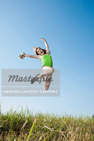 Teenaged girl jumping in mid-air over field, Germany Stock Photo - Premium Royalty-Free, Image code: 600-06899862