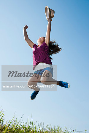 Girl holding hat, jumping in mid-air over field, Germany Stock Photo - Premium Royalty-Free, Image code: 600-06899864