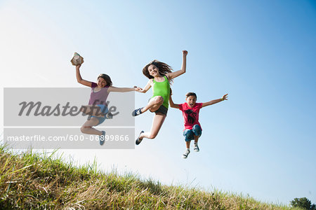Girls jumping in mid-air over field, Germany Stock Photo - Premium Royalty-Free, Image code: 600-06899866