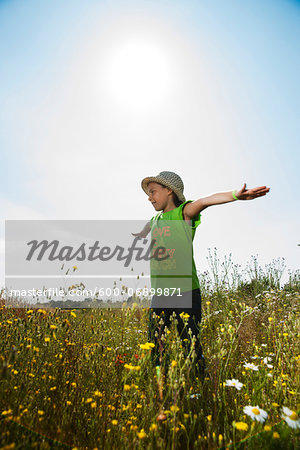 Girl standing in field with arms outstretched, Germany Stock Photo - Premium Royalty-Free, Image code: 600-06899871