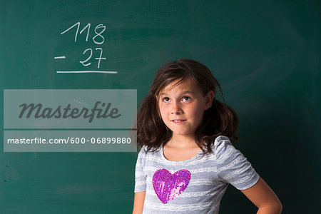 Portrait of girl standing in front of blackboard in classroom, Germany Stock Photo - Premium Royalty-Free, Image code: 600-06899880