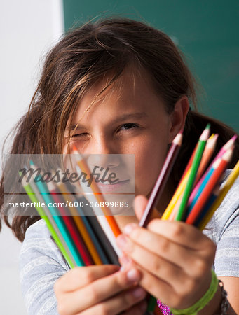 Close-up of girl holding colored pencils in hands, Germany Stock Photo - Premium Royalty-Free, Image code: 600-06899885