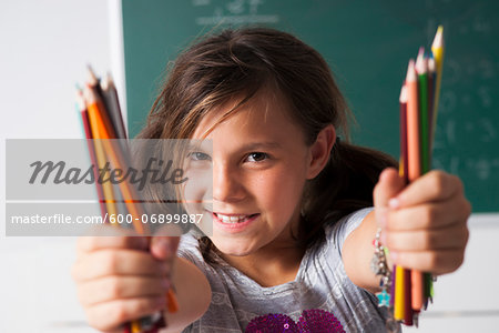 Close-up portrait of girl holding colored pencils in hands, Germany Stock Photo - Premium Royalty-Free, Image code: 600-06899887