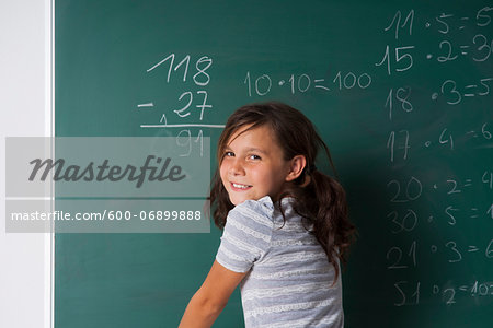 Girl standing in classroom in front of blackboard dong mathematical questions, Germany Stock Photo - Premium Royalty-Free, Image code: 600-06899888