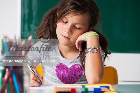 Girl sitting at desk in classroom, Germany Stock Photo - Premium Royalty-Free, Image code: 600-06899892