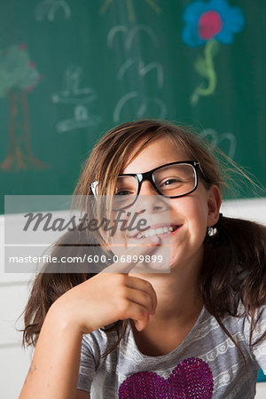 Close-up portrait of girl sitting at desk in classroom, Germany Stock Photo - Premium Royalty-Free, Image code: 600-06899899