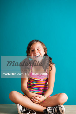 Portrait of girl sitting on floor, laughing, Germany Stock Photo - Premium Royalty-Free, Image code: 600-06899900