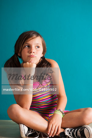Portrait of girl sitting on floor, pouting, Germany Stock Photo - Premium Royalty-Free, Image code: 600-06899902