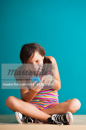Girl sitting on floor looking at smartphone, Germany Stock Photo - Premium Royalty-Free, Image code: 600-06899904