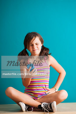 Girl sitting on floor looking at smartphone, Germany Stock Photo - Premium Royalty-Free, Image code: 600-06899905