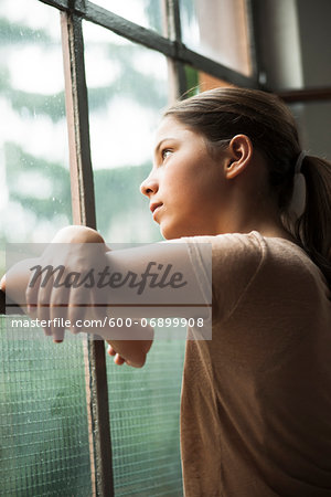 Girl looking out of window, Germany Stock Photo - Premium Royalty-Free, Image code: 600-06899908