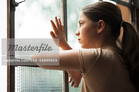 Girl looking out of window, Germany Stock Photo - Premium Royalty-Free, Image code: 600-06899909