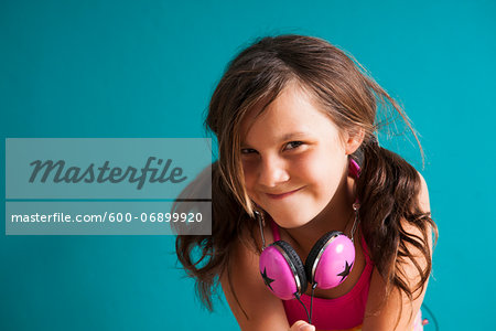 Portrait of girl wearing headphones around neck, looking at camera, making funny faces, Germany Stock Photo - Premium Royalty-Free, Image code: 600-06899920