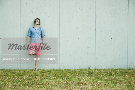Young man leaning on wall of building, wearing headphones and sunglasses, Germany Stock Photo - Premium Royalty-Free, Image code: 600-06899989
