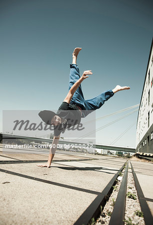 Teenaged boy doing handstand on cement road, freerunning, Germany Stock Photo - Premium Royalty-Free, Image code: 600-06900022