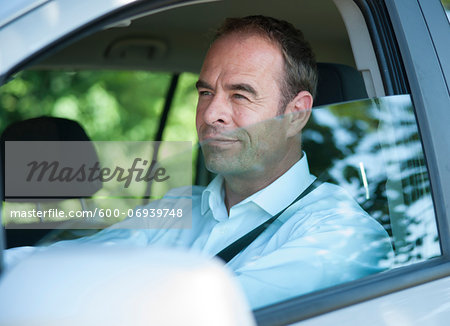 Businessman Driving Car, Mannheim, Baden-Wurttemberg, Germany Stock Photo - Premium Royalty-Free, Image code: 600-06939748