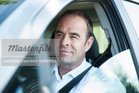 Businessman Driving Car, Mannheim, Baden-Wurttemberg, Germany Stock Photo - Premium Royalty-Free, Image code: 600-06939750