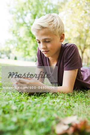 Boy Lying on Grass using Cell Phone, Mannheim, Baden-Wurttemberg, Germany Stock Photo - Premium Royalty-Free, Image code: 600-06939774