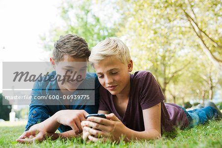 Boys using Cell Phone Outdoors, Mannheim, Baden-Wurttemberg, Germany Stock Photo - Premium Royalty-Free, Image code: 600-06939775