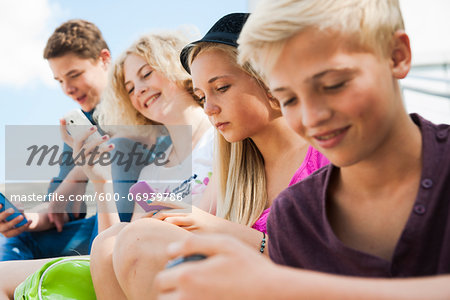 Teenagers using Cell Phones Outdoors, Mannheim, Baden-Wurttemberg, Germany Stock Photo - Premium Royalty-Free, Image code: 600-06939786
