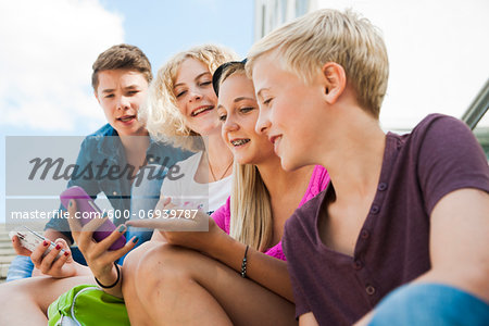 Teenagers using Cell Phones Outdoors, Mannheim, Baden-Wurttemberg, Germany Stock Photo - Premium Royalty-Free, Image code: 600-06939787