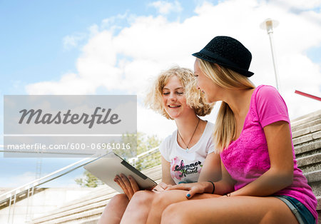 Teenage girls sitting on stairs outdoors, looking at tablet computer, Germany Stock Photo - Premium Royalty-Free, Image code: 600-06961016