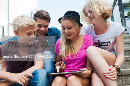 Group of teenagers sitting on stairs outdoors, looking at tablet computer, Germany Stock Photo - Premium Royalty-Free, Image code: 600-06961018
