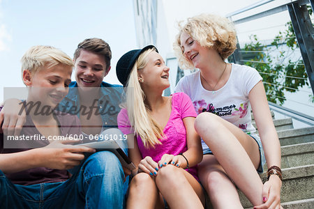 Group of teenagers sitting on stairs outdoors, looking at tablet computer, Germany Stock Photo - Premium Royalty-Free, Image code: 600-06961019