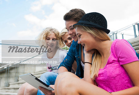 Group of teenagers sitting on stairs outdoors, looking at tablet computer, Germany Stock Photo - Premium Royalty-Free, Image code: 600-06961020