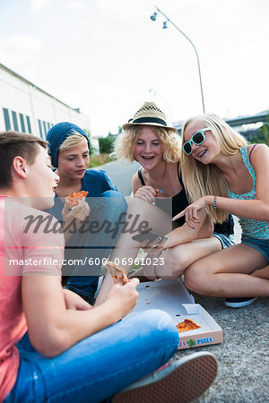 Group of Teenagers sitting on ground outdoors, eating pizza and hanging out, Germany Stock Photo - Premium Royalty-Free, Image code: 600-06961023