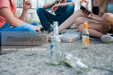 Surface level view of Group of teenagers sitting on ground outdoors, eating pizza and hanging out, Germany Stock Photo - Premium Royalty-Free, Image code: 600-06961024