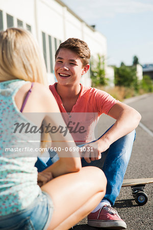 Teenage girl and teenage boy sitting on street, talking, Germany Stock Photo - Premium Royalty-Free, Image code: 600-06961031