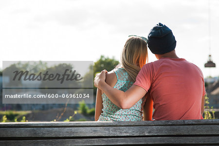 Backview of teenage boy with arm around teenage girl, sitting on bench outdoors, Germany Stock Photo - Premium Royalty-Free, Image code: 600-06961034