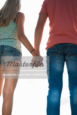 Backview of teenage boy and teenage girl holding hands, standing outdoors, Germany Stock Photo - Premium Royalty-Free, Image code: 600-06961036