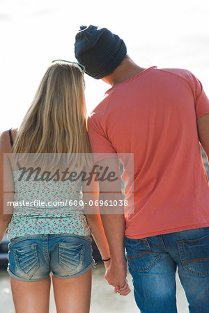 Backview of teenage boy and teenage girl holding hands, standing outdoors, Germany Stock Photo - Premium Royalty-Free, Image code: 600-06961038