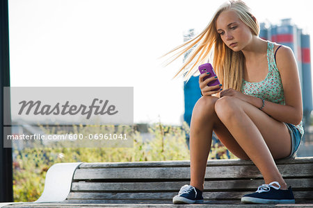 Teenage girl sitting on bench outdoors, looking at cell phone, Germany Stock Photo - Premium Royalty-Free, Image code: 600-06961041