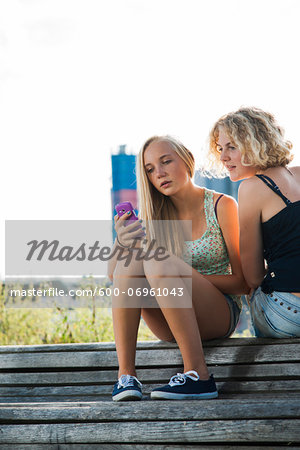 Teenage girls sitting on bench outdoors, looking at cell phone, Germany Stock Photo - Premium Royalty-Free, Image code: 600-06961043