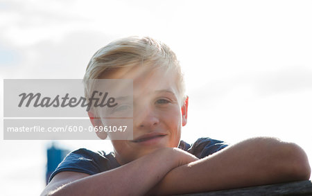 Close-up portrait of boy outdoors, smiling at camera, Germany Stock Photo - Premium Royalty-Free, Image code: 600-06961047