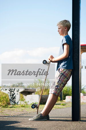 Portrait of boy outdoors with skateboard, standing on street, Germany Stock Photo - Premium Royalty-Free, Image code: 600-06961056