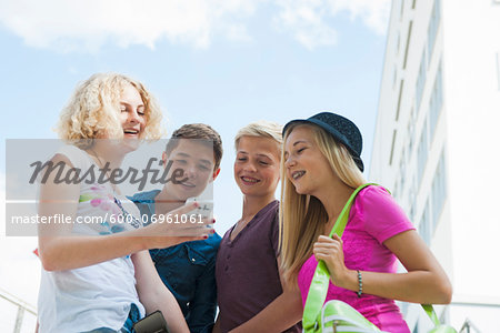 Group of teenagers standing outdoors looking at cell phone and talking, Germany Stock Photo - Premium Royalty-Free, Image code: 600-06961061