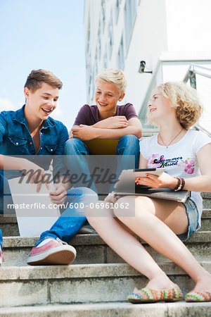 Teenagers sitting on stairs outdoors, talking and looking at tablet computer, Germany Stock Photo - Premium Royalty-Free, Image code: 600-06961062