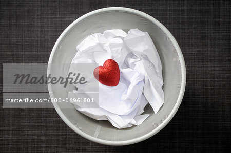 Heart shaped decoration with cruled paper in wastebasket Stock Photo - Premium Royalty-Free, Image code: 600-06961801