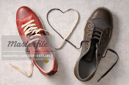 A man's shoe and a woman's shoe with laces tied together in a heart shape Stock Photo - Premium Royalty-Free, Image code: 600-06961803