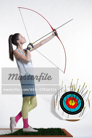 Side view of young, woman archer, aiming bow and arrow, studio shot on white background Stock Photo - Premium Royalty-Free, Image code: 600-07066926