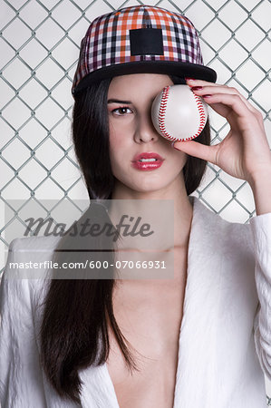 Close-up portrait of young woman wearing baseball cap and holding baseball in front of eye, studio shot on white background Stock Photo - Premium Royalty-Free, Image code: 600-07066931