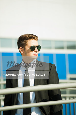 Young businessman wearing sunglasses, standing outdoors, Germany Stock Photo - Premium Royalty-Free, Image code: 600-07117108