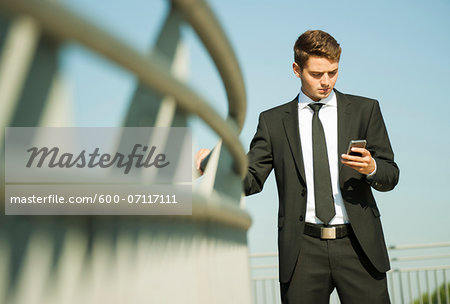Portrait of businessman standing by railing and looking at smartphone, Germany Stock Photo - Premium Royalty-Free, Image code: 600-07117111