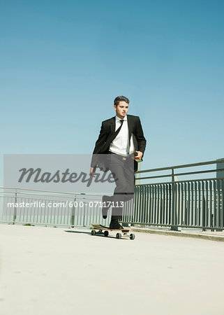 Businessman skateboarding on walkway holding binder, Germany Stock Photo - Premium Royalty-Free, Image code: 600-07117113